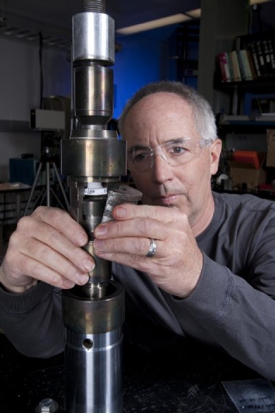 Sandia National Lab's Tom Crenshaw sets up a specimen in a test frame that will pull a solder joint apart to determine its tensile strength.  Crenshaw is a co-author of the paper noted below.  Click image for the largest view.