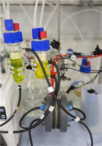 Lab set-up of a redox flow battery with the hydrophobic membrane (grey device at the bottom of the image) and two electrolyte reservoirs (bottles with yellow liquid). Image Credit: Philipp Scheffler at DWI. Click image for the largest view.