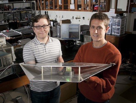 Duke's Hawkes & Katko the Metamaterial Researchers.  Duke engineering students Alexander Katko (left) and Allen Hawkes show a waveguide containing a single power-harvesting metamaterial cell, which provides enough energy to power the attached green LED.  Click image for the largest view.