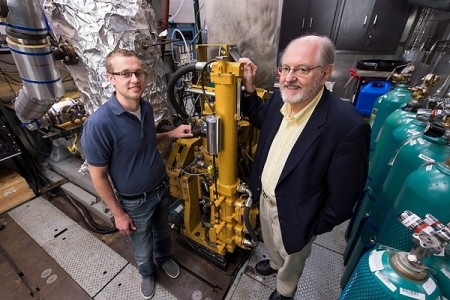 Sage Kokjohn, left, and Professor Reitz check a room with test monitors and air regulators that are connected to an operating, one-cylinder diesel engine in the Caterpillar Engine Lab at the Engineering Research Building.  Image Credit: Jeff Miller  Click image for the largest view.