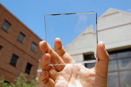 Solar power with a view: MSU doctoral student Yimu Zhao holds up a transparent luminescent solar concentrator module. Image Credit: Yimu Zhao, Michigan State.  Click image for the largest view.