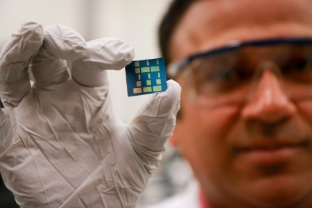 University of Utah materials science and engineering associate professor Ashutosh Tiwari holds up a substrate layered with a newly discovered 2-D material made of tin and oxygen. Tiwari and his team have discovered this new material, tin monoxide, which allows electrical charges to move through it much faster than common 3-D material such as silicon. This breakthrough in semiconductor material could lead to much faster computers and mobile devices such as smartphones that also run on less power and with less heat. Image Credit: Dan Hixson. University of Utah College of Engineering.