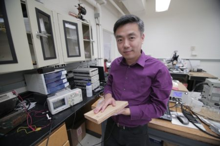 Associate Professor Xudong Wang holds a prototype of the researchers' energy harvesting technology, which uses wood pulp and harnesses nanofibers. The technology could be incorporated into flooring and convert footsteps on the flooring into usable electricity. Image Credit: Stephanie Precourt, University of Wisconsin-Madison.
